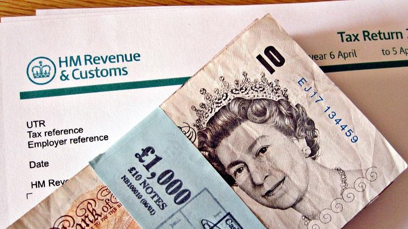 An image of an HMRC tax return with a bundle of £10 notes lying on top