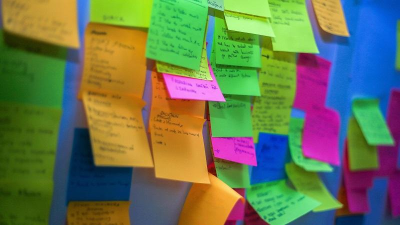 A close-up image of sticky notes stuck to a wall, in the style of agile development