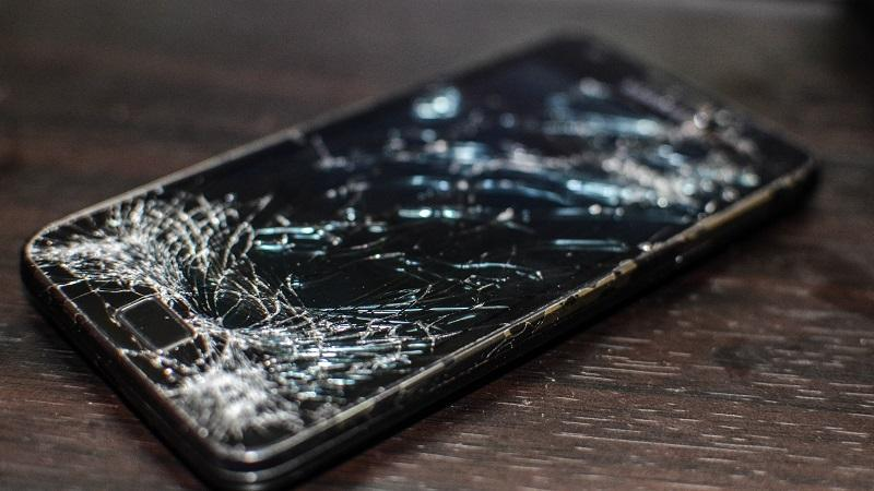 A close-up image of a smartphone with a heavily cracked screen