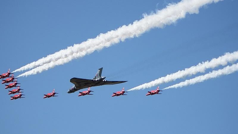 An image of RAF planes in flight, including several of aircraft from the Red Arrows aerobatics team