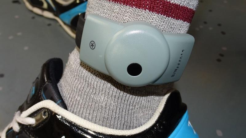 A close up image of an electronic tag attached to a wearer's ankle