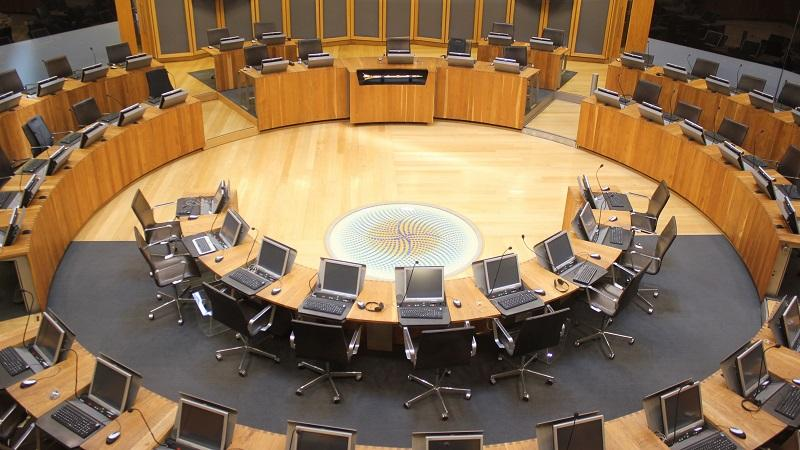 An image of the voting chamber of the Welsh Senedd, with chairs sitting empty