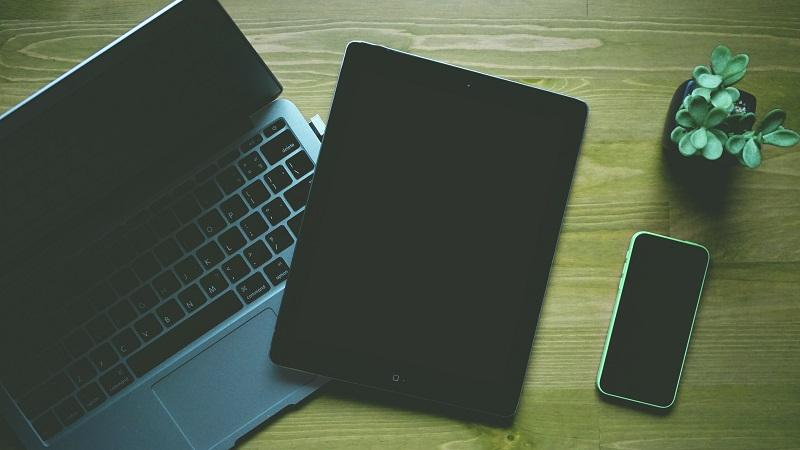 An image of a laptop, tablet and phone lying on a wooden surface, next to a small house plant