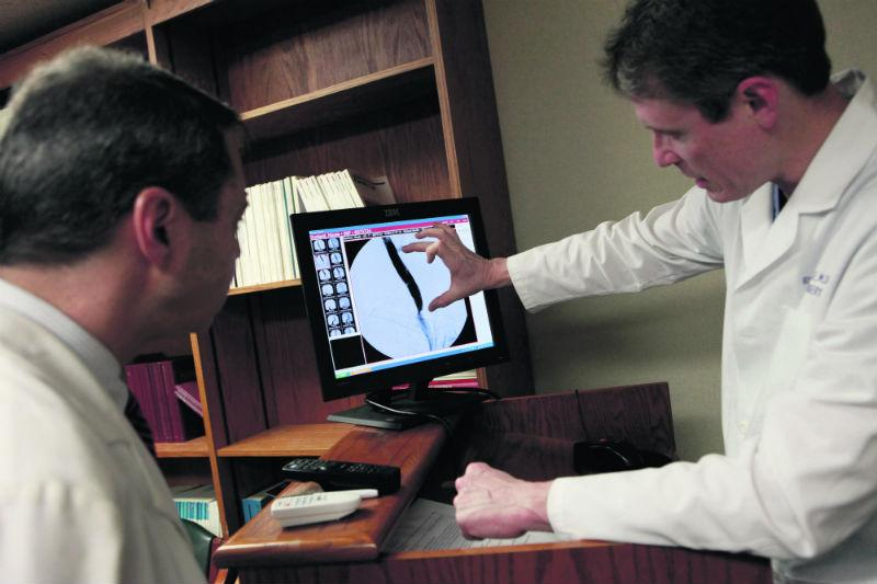image of two doctors sat at a desk looking at a computer screen