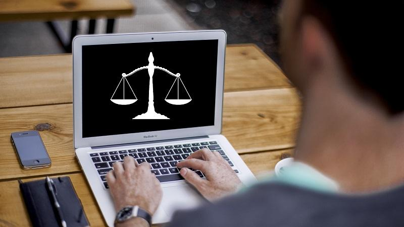 Image of justice scales on a laptop screen as man types on keyboard