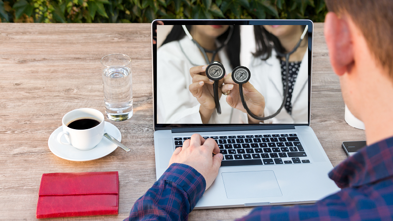 Image of two doctors holding a stethoscope up to a camera through a laptop screen