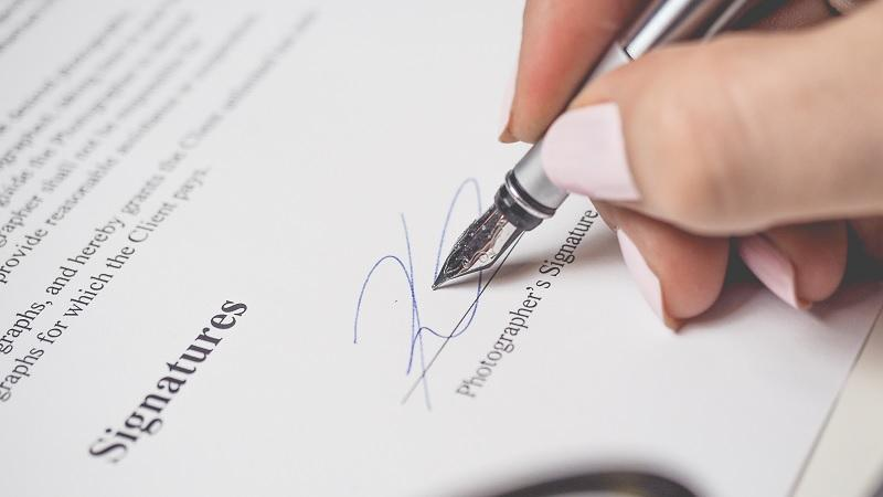 Close-up image of a woman signing a contract