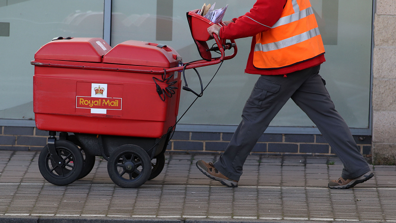 A post man delivers letters in Woking, Surrey