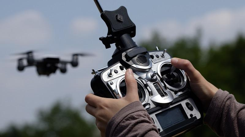 A close-up image of hands using a drone controller with the drone itself in the near distance