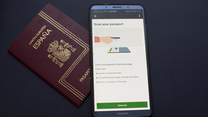 An image of the Settled Status app on a smartphone, lying next to a Spanish passport