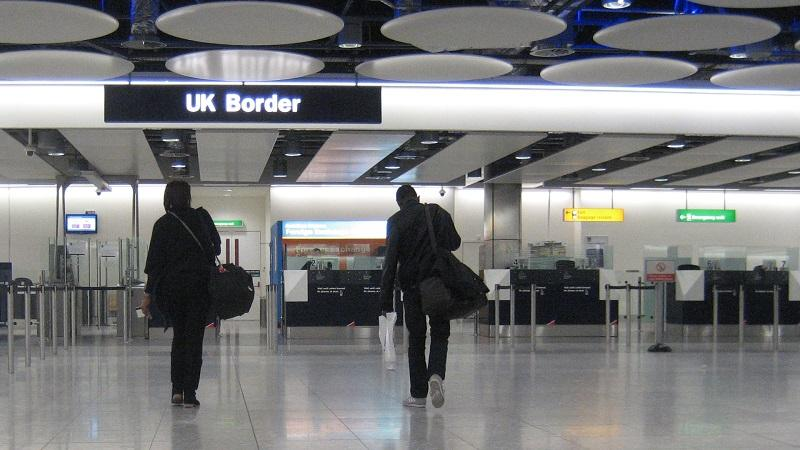 An image of two air passengers walking towards the UK border