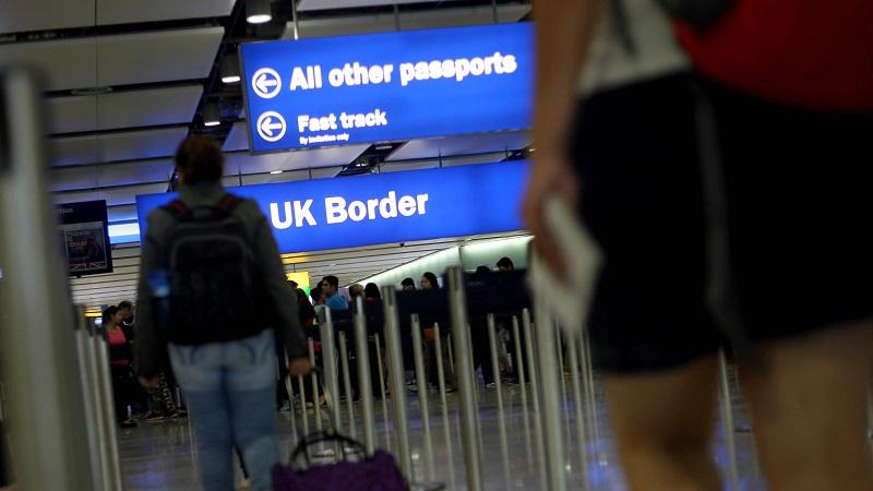 An image of travellers at an airport approaching the UK border