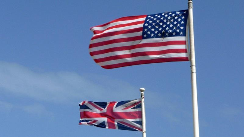 An image of UK and US flags hanging on flagpoles