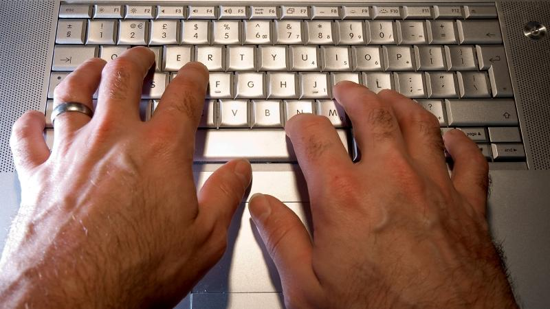A man typing on a laptop computer